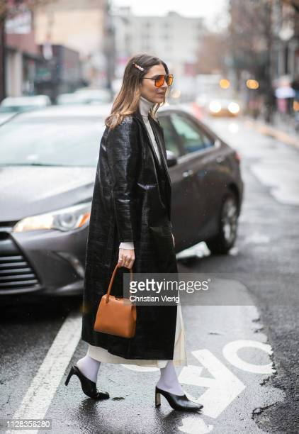A guest is seen wearing black coat turtleneck brown bag hair clip outside Nanushka during New York Fashion Week Autumn Winter 2019 on February 08...