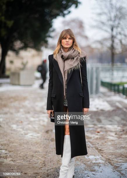 A guest is seen wearing black coat white boots outside Alexandre Vauthier during Haute Couture Spring Summer 2019 Day Two on January 22 2019 in Paris...