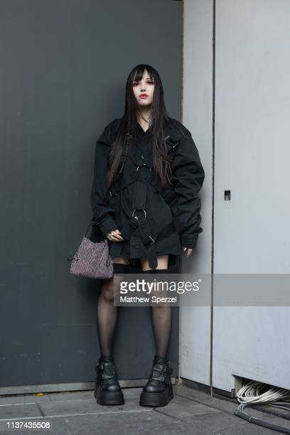 A guest is seen wearing black dress black platforms with grey bag during the Amazon Fashion Week TOKYO 2019 A/W on March 21 2019 in Tokyo Japan