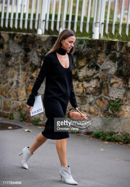 Guest is seen wearing black dress, striped Loewe bag outside Loewe during Paris Fashion Week Womenswear Spring Summer 2020 on September 27, 2019 in...