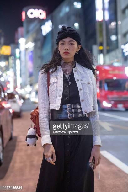 A guest is seen wearing black dress triple belts white jacket black head scarf during the Amazon Fashion Week TOKYO 2019 A/W on March 21 2019 in...