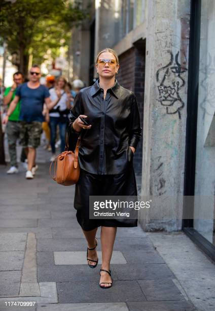 A guest is seen wearing black leather button shirt skirt brown bag outside Marques Almeida during London Fashion Week September 2019 on September 14...