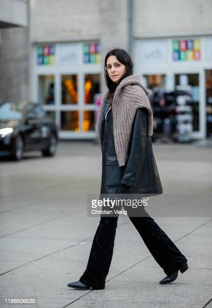 A guest is seen wearing black leather coat knit velvet flared pants during the Berlin Fashion Week Autumn/Winter 2020 on January 14 2020 in Berlin...