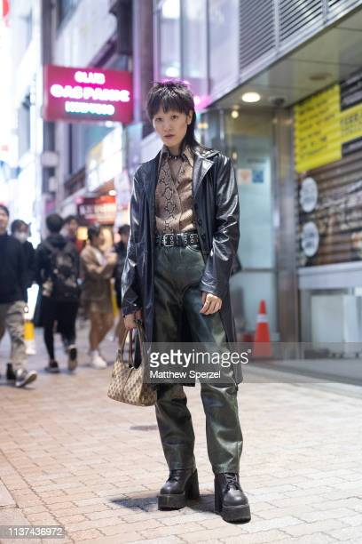 A guest is seen wearing black leather coat reptile print shirt green leather pants belt and black boots with Gucci bag during the Amazon Fashion Week...