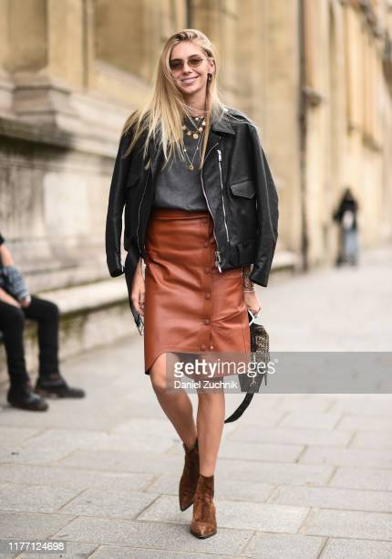 A guest is seen wearing black leather jacket gray top and brown leather skirt outside the Unravel show during Paris Fashion Week SS20 on September 25...
