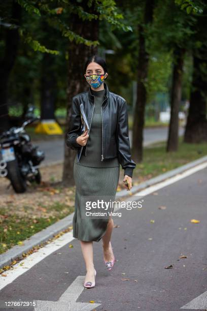 Guest is seen wearing black leather jacket, olive green turtleneck and skirt, face mask outside Sportmax during the Milan Women's Fashion Week on...