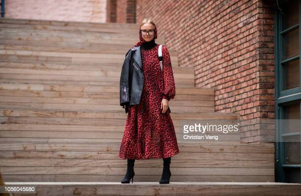 A guest is seen wearing black leather jacket red dress with animal print and hood during MercedesBenz Tbilisi Fashion Week on November 1 2018 in...