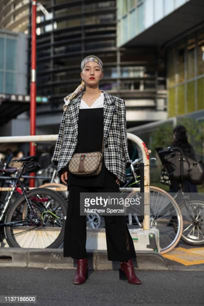 Guest is seen wearing black plaid blazer, black dress and white shirt with Gucci bag and bandana during the Amazon Fashion Week TOKYO 2019 A/W on...
