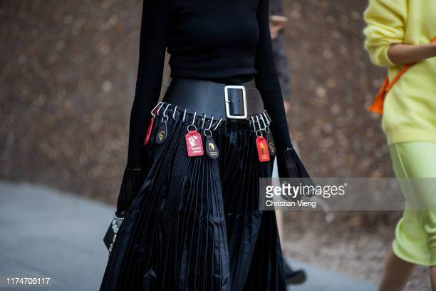Guest is seen wearing black pleated skirt, belt with bags, top outside Ports 1961 during London Fashion Week September 2019 on September 14, 2019 in...