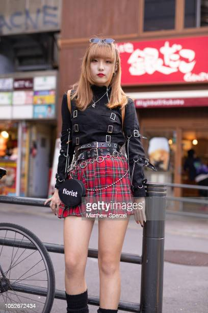 A guest is seen wearing black shirt with buckles red plaid skirt multiple belts and chains and black platform boots during the Amazon Fashion Week...