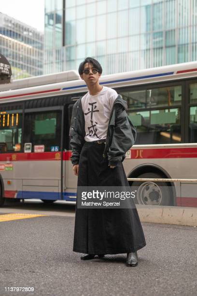 A guest is seen wearing black skirt grey jacket white shirt with kanji during the Amazon Fashion Week TOKYO 2019 A/W on March 23 2019 in Tokyo Japan