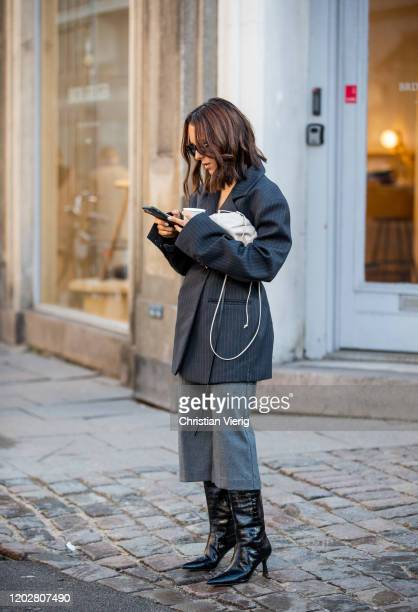 Guest is seen wearing black striped blazer, white bag, cropped pants, black boots outside REMAIN Birger Christensen during Copenhagen Fashion Week...