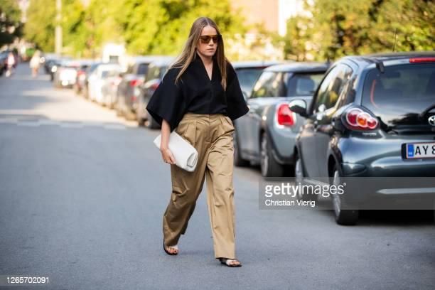 Guest is seen wearing black top, beige pants, white bag outside By Malene Birger during Copenhagen Fashion Week Spring/Summer 2021 on August 12, 2020...