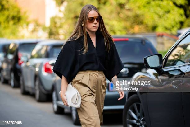 Guest is seen wearing black top, beige pants, white bag outside By Malene Birger during Copenhagen Fashion Week Spring/Summer 2021 on August 12, 2020...