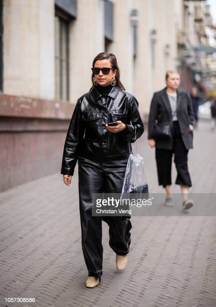 A guest is seen wearing black vinyl jacket and pants during MercedesBenz Tbilisi Fashion Week on November 4 2018 in Tbilisi Georgia