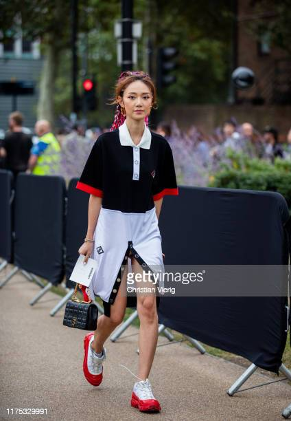 Guest is seen wearing black white red skirt with slit and polo shirt outside Burberry during London Fashion Week September 2019 on September 16, 2019...