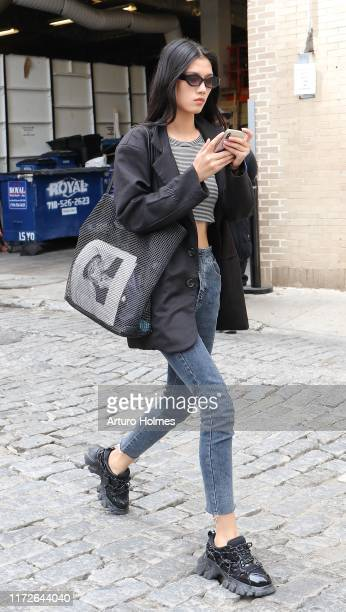 Guest is seen wearing blacked and white shirt, black short trench coat, grey jeans, black designer sneakers and black mesh bag during New York...