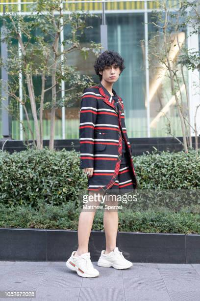 A guest is seen wearing black/red stripe jacket with Gucci sneakers during the Amazon Fashion Week TOKYO 2019 S/S on October 20 2018 in Tokyo Japan
