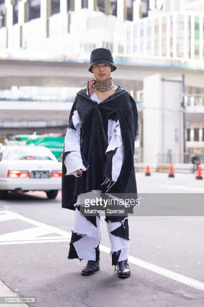 A guest is seen wearing black/white layered denim outfit with bucket hat and scarf during the Amazon Fashion Week TOKYO 2019 S/S on October 20 2018...