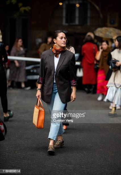 Guest is seen wearing blazer, scarf, denim jeans, orange bag during day 1 of the Mercedes-Benz Tbilisi Fashion Week on October 31, 2019 in Tbilisi,...