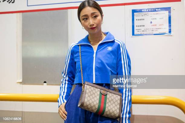 A guest is seen wearing blue Adidas track suit with Gucci bag during the Amazon Fashion Week TOKYO 2019 S/S on October 17 2018 in Tokyo Japan