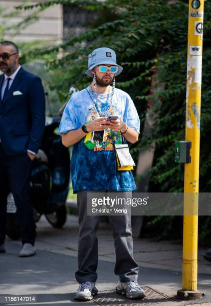 A guest is seen wearing blue bucket hat outside M1992 during the Milan Men's Fashion Week Spring/Summer 2020 on June 15 2019 in Milan Italy