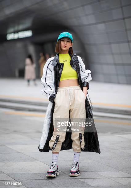 A guest is seen wearing blue cap cropped top beige pants white socks Balenciaga sneaker black white coat at the Hera Seoul Fashion Week 2019 F/W at...