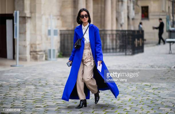 A guest is seen wearing blue coat beige high waist pants outside Thom Browne during Paris Fashion Week Womenswear Fall/Winter 2019/2020 on March 03...