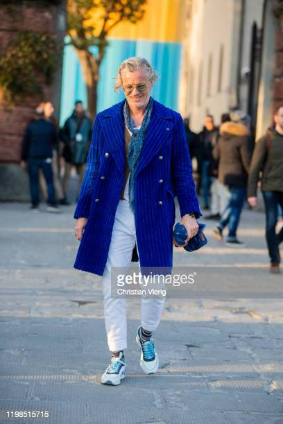 A guest is seen wearing blue corduroy coat white pants during Pitti Uomo 97 at Fortezza Da Basso on January 09 2020 in Florence Italy