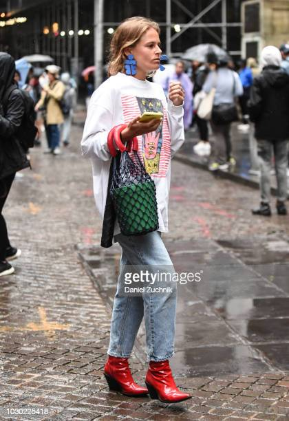 A guest is seen wearing blue earrings red shoes blue jeans and graphic print shirt outside the Tibi show during New York Fashion Week Women's S/S...