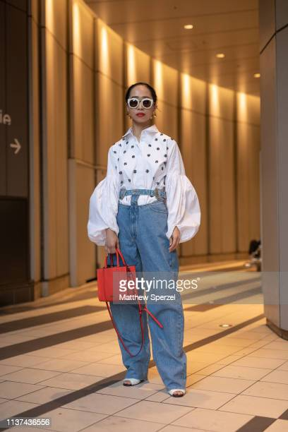 A guest is seen wearing blue jeans white spotted shirt orange bag and sunglasses during the Amazon Fashion Week TOKYO 2019 A/W on March 21 2019 in...
