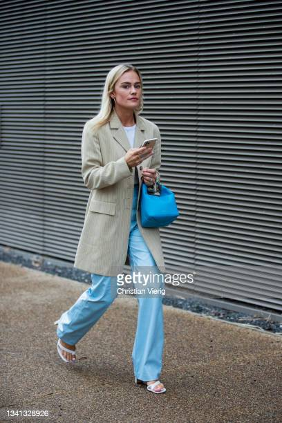 Guest is seen wearing blue pants and bag, blazer outside Rejina Pyo during London Fashion Week September 2021 on September 19, 2021 in London,...