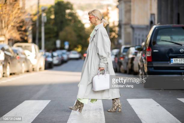 A guest is seen wearing boots with snake print white bag grey trench coat mint green asymmetric dress during MercedesBenz Tbilisi Fashion Week on...