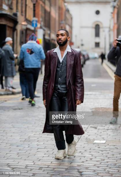 A guest is seen wearing boredeaux leather coat black pants during London Fashion Week Men's January 2020 on January 05 2020 in London England