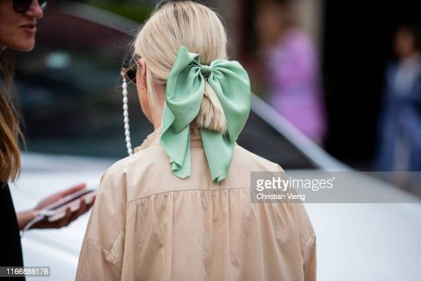 A guest is seen wearing bow tie in her hair outside Lala Berlin during Copenhagen Fashion Week Spring/Summer 2020 on August 08 2019 in Copenhagen...