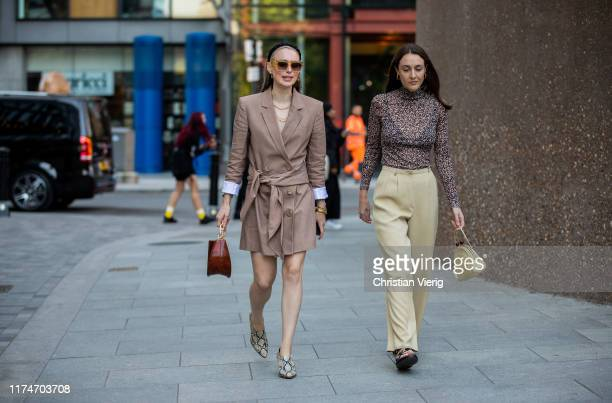 Guest is seen wearing brown belted coat and a guest wearing sheer top, yellow pants outside Ports 1961 during London Fashion Week September 2019 on...