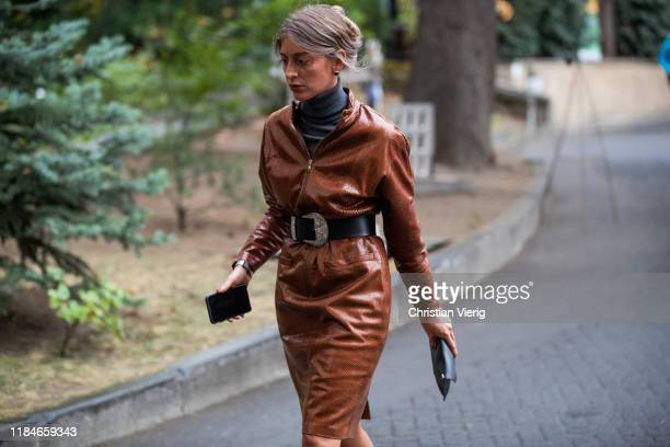 A guest is seen wearing brown belted coat during day 1 of the MercedesBenz Tbilisi Fashion Week on October 31 2019 in Tbilisi Georgia