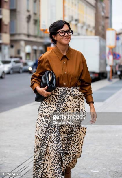 Guest is seen wearing brown button shirt, asymmetric skirt with animal print, black Bottega Veneta pouch bag outside the Max Mara show during Milan...