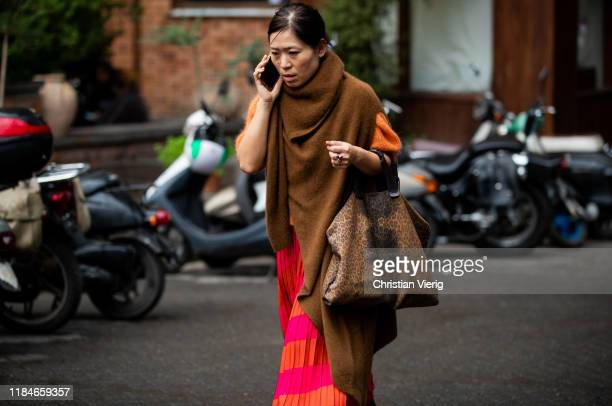 A guest is seen wearing brown cashmere scarf bag with leopard print orange red skirt during day 1 of the MercedesBenz Tbilisi Fashion Week on October...