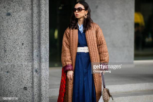 A guest is seen wearing brown coat navy striped dress during MercedesBenz Tbilisi Fashion Week on November 5 2018 in Tbilisi Georgia