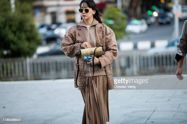 A guest is seen wearing brown jacket track suit zipped jacket pleated skirt during day 3 of the MercedesBenz Tbilisi Fashion Week on November 02 2019...