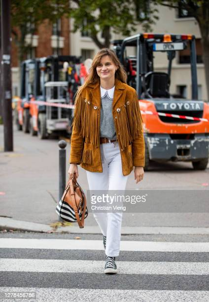 Guest is seen wearing brown jacket with fringes, Loewe bag, white pants outside Hermes during Paris Fashion Week - Womenswear Spring Summer 2021 :...