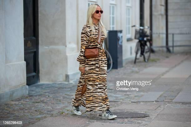 Guest is seen wearing brown Loewe bag, dress with tiger print outside Baum und Pferdgarten during Copenhagen Fashion Week Spring/Summer 2021 on...