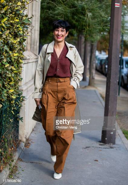A guest is seen wearing brown pants grey trench coat button up shirt in bordeaux outside Lacoste during Paris Fashion Week Womenswear Spring Summer...