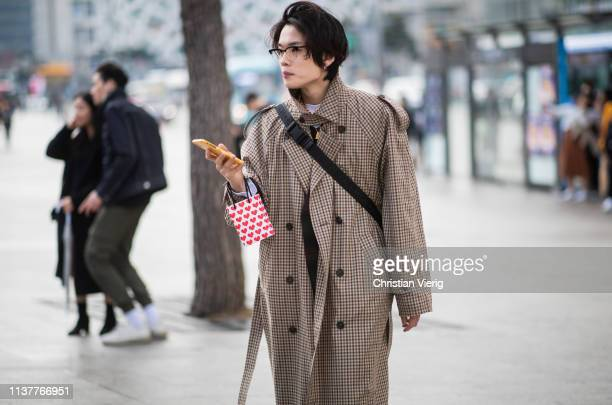 A guest is seen wearing brown plaid coat at the Hera Seoul Fashion Week 2019 F/W at Dongdaemun Design Plaza at Dongdaemun Design Plaza on March 23...