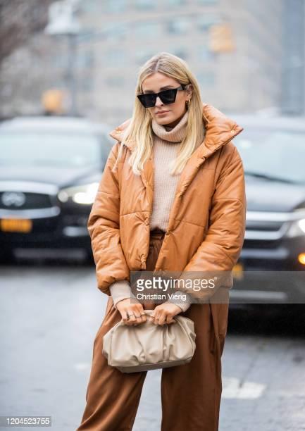 Guest is seen wearing brown puffer jacket, pants, clutch, turtleneck outside Tadashi Shoji during New York Fashion Week February 2020 on February 06,...