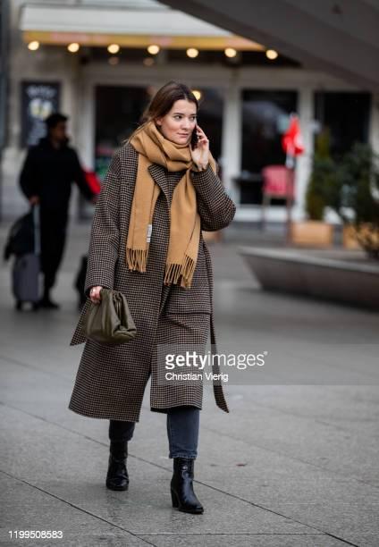A guest is seen wearing brown scarf wool coat olive Bottega Veneta Pouch bag dark denim jeans during the Berlin Fashion Week Autumn/Winter 2020 on...
