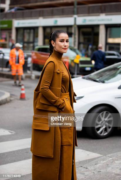Guest is seen wearing brown sleeveless coat with pockets, turtleneck, high waist pants outside the Max Mara show during Milan Fashion Week...