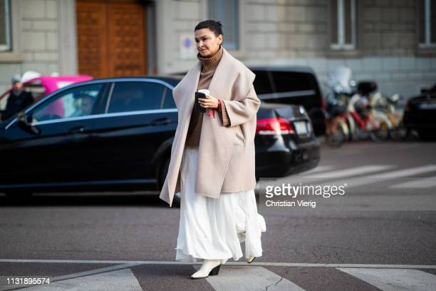 Guest is seen wearing brown turtleneck, cape, white skirt outside Ferragamo on Day 4 Milan Fashion Week Autumn/Winter 2019/20 on February 23, 2019 in...