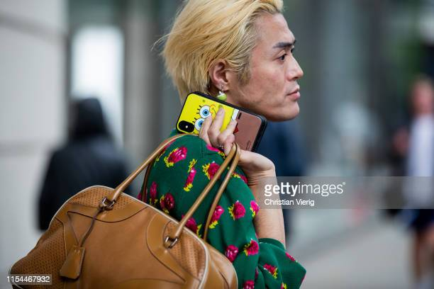A guest is seen wearing brown weekender bag Spongebob phone case outside Kiko Kostadinov during London Fashion Week Men's June 2019 on June 07 2019...